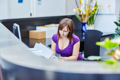 Beautiful young receptionist at work Stock Photography