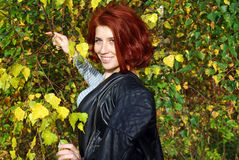 The beautiful young red girl poses near autumn trees. Warm autumn day Stock Photos