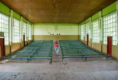 Beautiful young red hair girl at the abandoned conference hall in Ukraine. Beautiful young red hair girl in the pink t-shirt at the abandoned conference hall in Stock Image