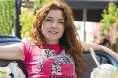 Beautiful young red hair girl looking in camera. Beautiful young red hair girl in the pink t-shirt and jeans looking in the camera Royalty Free Stock Photos
