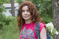 Beautiful young red hair girl lost while hiking. Beautiful young red hair girl in the pink t-shirt lost while hiking Stock Photo