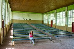 Beautiful young red hair girl sitting at the abandoned conference hall in Ukraine. Beautiful young red hair girl  in the pink t-shirt sitting at the abandoned Royalty Free Stock Photography