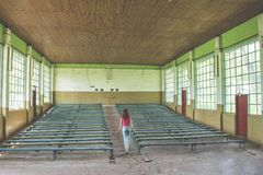 Beautiful young red hair girl walking at the abandoned conference hall in Ukraine. Beautiful young red hair girl in the pink t-shirt walking at the abandoned Stock Images