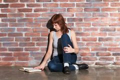 Beautiful young red hair woman in jeans with book sitting on floor near brick wall. Attentively reading an interesting Stock Photography