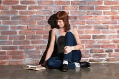 Beautiful young red hair woman in jeans with book sitting on floor near brick wall. Attentively reading an interesting Royalty Free Stock Photo