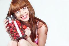 Beautiful young red hair woman with strawberries. Beautiful young sensible red-hair, blue eyes woman wearing pink underwear strawberries eating them from the can royalty free stock photos