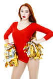 Beautiful young red-haired cheerleader in a red uniform Royalty Free Stock Photo