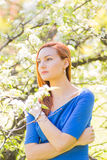 Beautiful young red-haired girl in blue dress among spring flowe Stock Photography