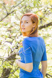 Beautiful young red-haired girl in blue dress among spring flowe Stock Image