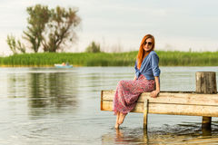 Beautiful young red haired girl in colorful long sarafan dress stands on a stump on a wooden pier on a river or lake. Green bulrus Stock Photography