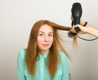 Beautiful young red-haired girl at the hairdresser makes blow drying, shorn bangs, hair polishing Royalty Free Stock Images