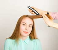 Beautiful young red-haired girl at the hairdresser makes blow drying, shorn bangs, hair polishing Stock Photos