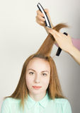 Beautiful young red-haired girl at the hairdresser makes blow drying, shorn bangs, hair polishing Stock Photography