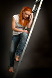 Young red-haired girl leaning on a ladder Stock Photos