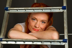 Beautiful young red-haired girl leaning on a ladder Stock Photo