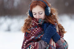 Beautiful young red-haired woman in blue headphones and gloves. She is wrappening in a big scarf with ethnic pattern. She is shy. There is some snow in her stock images