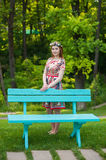 Beautiful young red-haired woman in a bright blue dress standing near a bench in the garden Royalty Free Stock Images