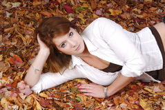 Beautiful young red haired woman lying in autumn l Royalty Free Stock Image