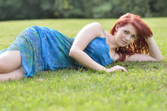 Beautiful young red haired woman outside in summer Stock Images