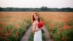 Beautiful young red-haired woman in poppy field holding a bouquet of poppies. With their eyes closed Stock Photo