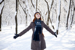 Beautiful young red-haired woman in winter park. Outdoor shot Royalty Free Stock Photo