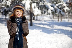 Beautiful young red-haired woman in winter park. Outdoor shot Royalty Free Stock Photography
