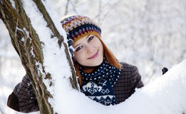 Beautiful young red-haired woman in winter park.  Stock Photo