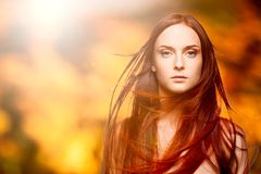 Beautiful young red woman over autumn background Royalty Free Stock Photography