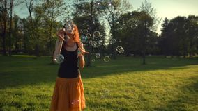 Beautiful young redhair girl blowing soap bubbles outdoors. Sunset stock video