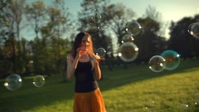 Beautiful young redhair girl blowing soap bubbles outdoors. Sunrise stock video footage