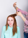 Beautiful young redhaired model in salon, hairdresser does a hairstyle. trims the hair tips with scissors.  royalty free stock photo