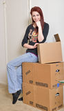 Beautiful young redhaired woman sits with moving boxes Royalty Free Stock Photography