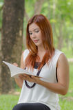 Beautiful young redhead Asian woman reading a book Royalty Free Stock Images