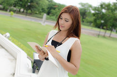 Beautiful young redhead Asian woman reading a book Stock Image