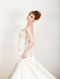 Beautiful young redhead bride wearing white wedding dress with professional make-up and hairstyle Stock Photo