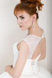 Beautiful young redhead bride wearing white wedding dress with professional make-up and hairstyle Royalty Free Stock Photo