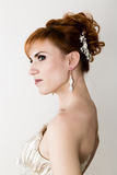 Beautiful young redhead bride wearing white wedding dress with professional make-up and hairstyle Stock Image