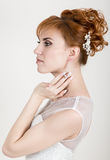 Beautiful young redhead bride wearing white wedding dress with professional make-up and hairstyle Stock Images