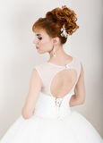 Beautiful young redhead bride wearing white wedding dress with professional make-up and hairstyle.  Stock Photo