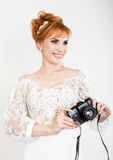 Beautiful young redhead bride wearing white wedding dress with professional make-up and hairstyle. holding camera Royalty Free Stock Photos
