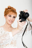 Beautiful young redhead bride wearing white wedding dress with professional make-up and hairstyle. holding camera Stock Images