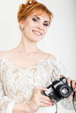 Beautiful young redhead bride wearing white wedding dress with professional make-up and hairstyle. holding camera Stock Image
