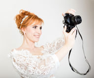 Beautiful young redhead bride wearing white wedding dress with professional make-up and hairstyle. holding camera Stock Photo