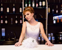 Beautiful young redhead bride wearing white wedding dress with professional make-up and hairstyle standing at bar.  Stock Photo
