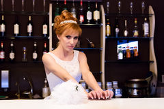 Beautiful young redhead bride wearing white wedding dress with professional make-up and hairstyle standing at bar.  Royalty Free Stock Photo