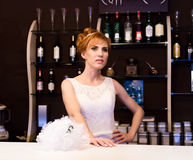 Beautiful young redhead bride wearing white wedding dress with professional make-up and hairstyle standing at bar.  Royalty Free Stock Photography