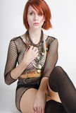 Beautiful young redhead female wearing fishnet top Royalty Free Stock Image