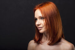 Beautiful young redhead girl with attitude, strong portrait on dark background. Stock Photography