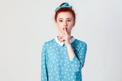 The beautiful young redhead girl, holding index finger at lips, raising brows, saying `Shh`, `Hush`, `Tsss`. Studio shot on gray background stock images