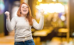 Young beautiful redhead woman  over white background. Beautiful young redhead woman happy and excited expressing winning gesture. Successful and celebrating Royalty Free Stock Photography
